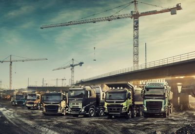 Six Volvo Group trucks lined up at a construction site underneath a bridge