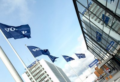 Five blue Volvo flags flickering in the wind in front of a Volvo building