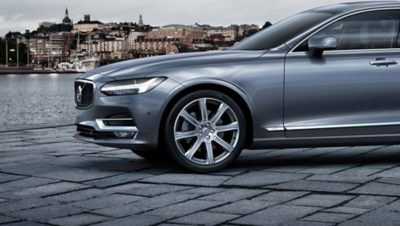 A grey Volvo car parked on a street by the water