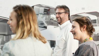 Tre medarbetare från Volvo Group i ett digital rum fyllt av visionsbilder av förarhytter
