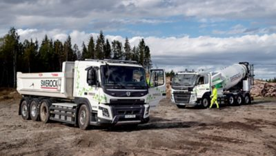The Volvo FM and Volvo FMX electric trucks off road on muddy ground with trees in the background.