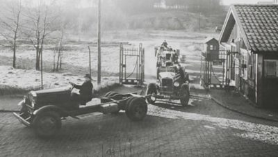 A line of old Volvo trucks driving through a gate