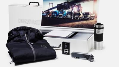 Volvo Group merchandise: jacket, coffee mug, Volvo truck toy, lighter, picture of Volvo trucks
