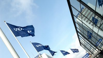 Five blue Volvo flags in front of a Volvo Group building