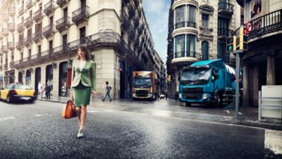 Two Volvo trucks waiting for the trafficlight to turn green in a crossing