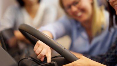 People touching a steering wheel