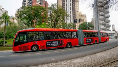 Red Volvo bus with eight wheel sets in Curitibia, Brazil