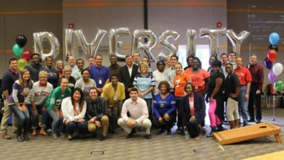 A diversity networks employee resource group in front of nine balloons spelling DIVERSITY
