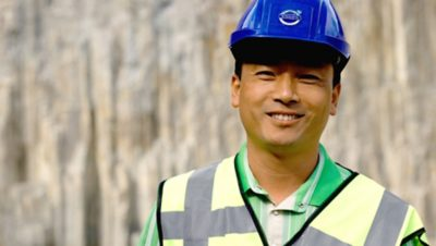 Volvo Group worker at a construction site wearing a blue helmet and a yellow safety west