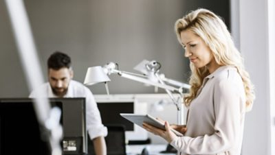 Two Volvo Group employees, one working on her tablet, the other one working on his computer