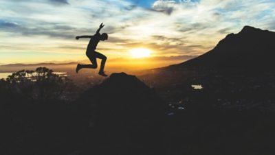 En person hoppar på ett berg i skymningen