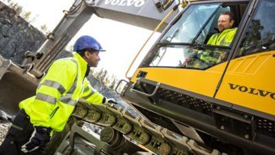 Kierowca żółtej koparki Grupy Volvo na placu budowy rozmawia ze współpracownikiem stojącym na ziemi
