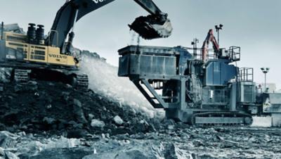Желтый экскаватор Volvo Group опрокидывает полный ковш камней в камнедробилку