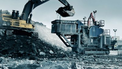 Gele graafmachine van de Volvo Group die een laadschoep vol keien in een steenbreker (crusher) leegt