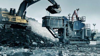 Gele graafmachine van de Volvo Group die zijn graafbak vol stenen in een steenbreker leegt