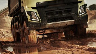 Pearl white industrial Volvo Group truck driving off road through mud and water