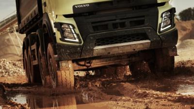 Parelwitte industriële truck van de Volvo Group rijdt off-road door modder en water