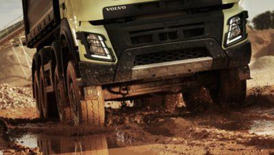 Parelwitte industriële truck van de Volvo Group rijdt op onverharde wegen door modder en water