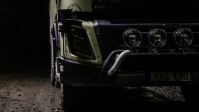 The front of a green Volvo truck driving through mud at night