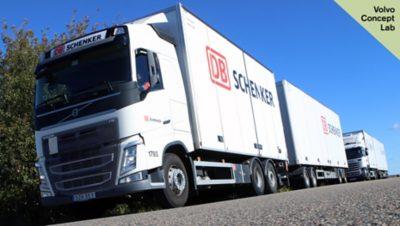 A line of white DB Schenker trucks