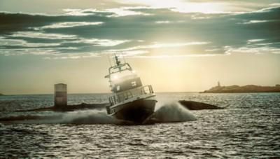 Gros bateau à moteur effectuant un virage serré créant une grosse vague en mer