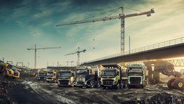 Six Volvo trucks lined up at a construction site beneath a bridge next to two wheel loaders