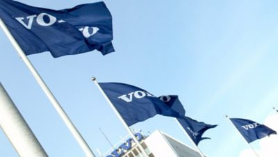 Four Volvo Group flags flickering in the wind with a Volvo building in the background