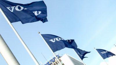 Cuatro banderas de Volvo Group flameando en el viento con un edificio de Volvo en el fondo