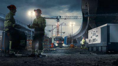 Dos trabajadores de Volvo Group conversando en un sitio de construcción de Volvo