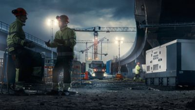 Twee medewerkers van de Volvo Group in gesprek op een bouwlocatie van Volvo