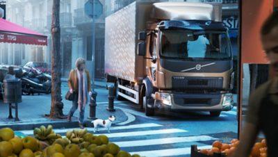 브론즈 컬러의 Volvo Group 트럭이 목줄을 한 개를 데리고 사람이 횡단보도를 건너는 것을 기다리고 있습니다.