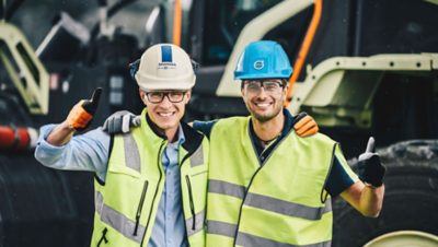 Volvo construction equipment worker and Skanska worker with their arms around each other giving the thumbs up