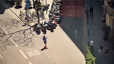 A skateboarder in the middle between two roads with mopeds parked behind him on the street and bikes on the pavement