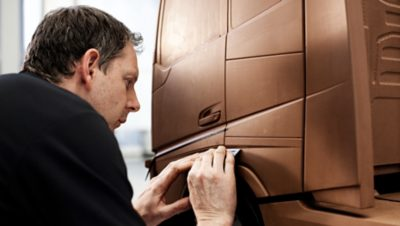 Volvo Group employee constructing a bronze colored model of a Volvo truck