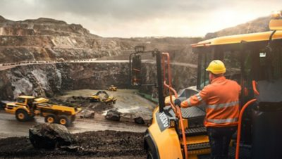 Worker standing on the step of a yellow Volvo Group truck overlooking an excavation site