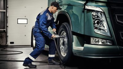 Volvo Group worker in a blue overall tightening the wheel bolts on a blue-green Volvo truck