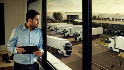 Volvo Group employee with a tablet in his hands looking out through a window over a lot filled with Volvo trucks