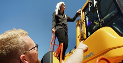 Girl standing on a yellow machine
