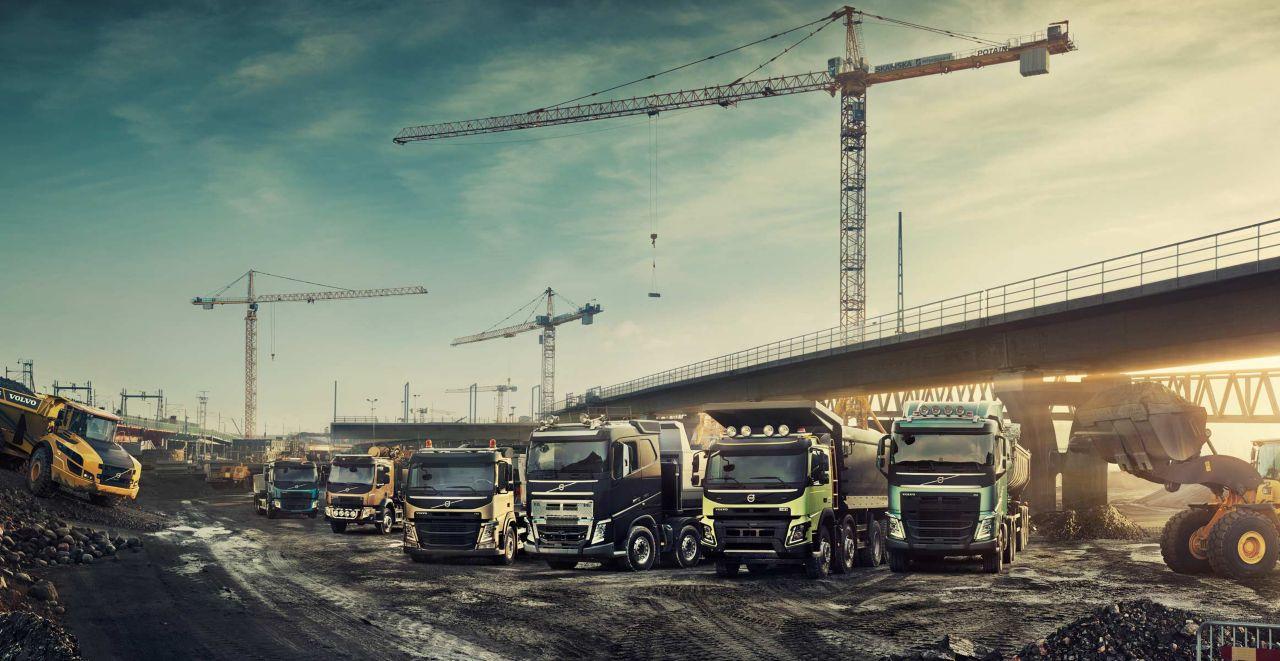 Sechs Volvo Lkw in einer Reihe auf einer Baustelle unter einer Brücke neben zwei Radladern