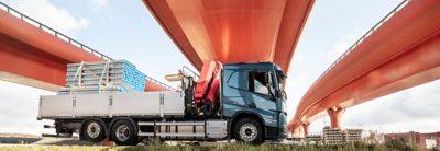 A truck parked under an overpass