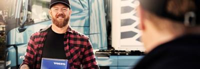 Egy járművezető egy Eredeti Volvo Alkatrész kék dobozát tartja a kezében, miközben valakivel beszélget