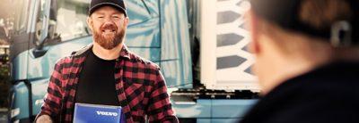 Ein Fahrer hält einen blauen Volvo Originalteilekarton in Händen, während er mit jemandem spricht