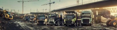 Six Volvo trucks lined up at a construction site beneath a bridge
