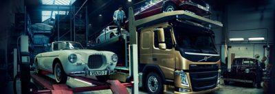 Voiture particulière Volvo Blanche rétro sur un pont élévateur à côté d'un camion Volvo de couleur Bronze transportant deux voitures, une rouge et une blanche
