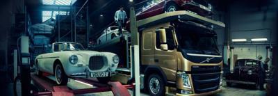 Weißer Volvo Oldtimer neben einem bronzefarbenen Volvo Lkw, der einen roten und einen weißen Pkw geladen hat