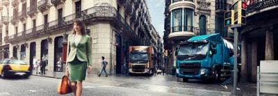 A crossing filled with people and two Volvo trucks waiting for the light to turn green
