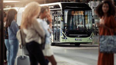 야외 레스토랑 좌석으로 둘러싸인 도로에서 Lindholmen 과학 공원으로 향하는 진주처럼 흰 Volvo Group 버스