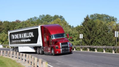 """Red Mack truck with the message """"I'm one in a million"""" on its payload on a road in Allentown, USA"""