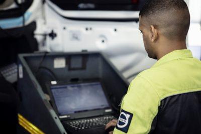 Un técnico de servicio de Volvo sostiene una computadora junto a un camión