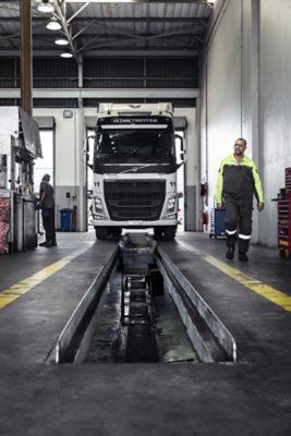 Un técnico de servicio de Volvo sosteniendo una computadora mira un camión